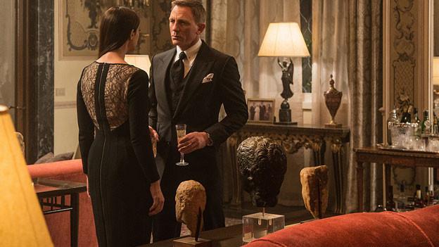 Daniel Craig alias James Bond im Gespräch mit einer Frau, in der Hand hält er ein Glas Champagner.