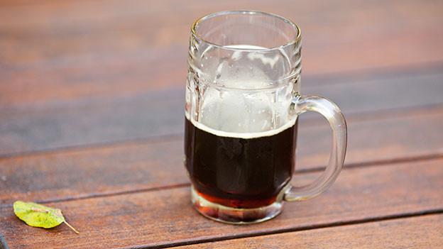Ein Glas mit dunklem Bier.