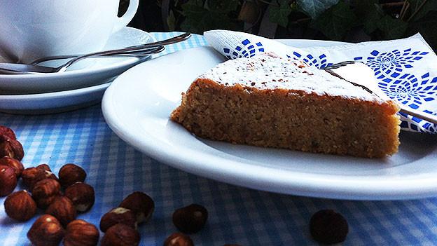 Ein Stück Haselnuss-Kuchen auf weissen Teller angerichtet.