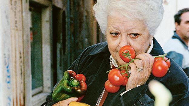 Frau riecht an Tomaten.