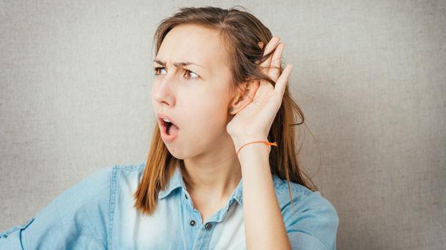 Frau hält Hand ans Ohr und signalisiert, dass sie etwas nicht verstanden hat.