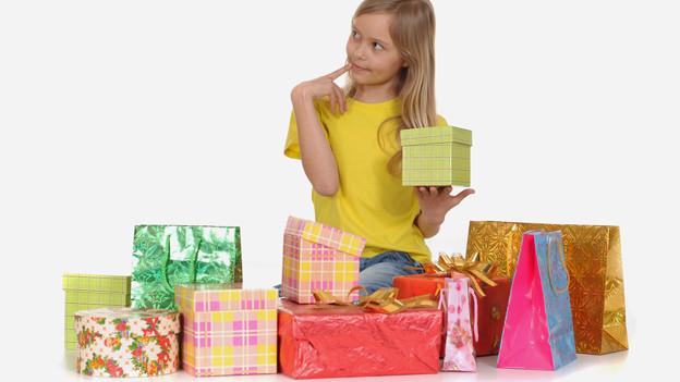Ein Mädchen sitzt neben vielen Geschenken und hält eines davon in der Hand.