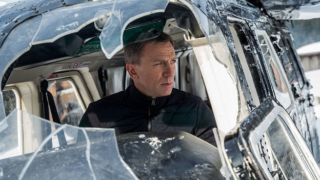 James Bond sitzt hinter einer zerschlagenen Scheibe.