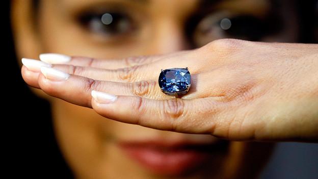 Der blaue Diamant an einer Frauenhand.
