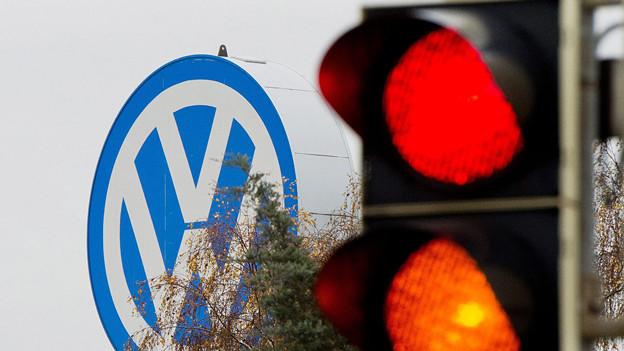 Das VW-Logo, im Vordergrund eine Ampel, die auf rot steht.