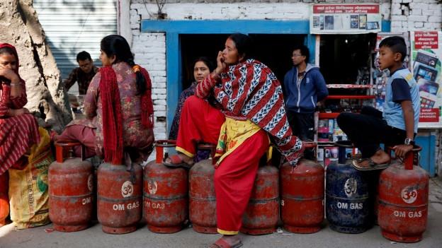 Frauen und Kinder sitzen auf leeren Gasflaschen.