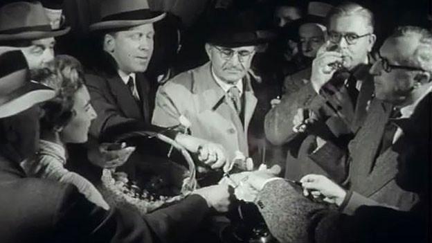Männer in den 1950er-Jahren essen Fondue.