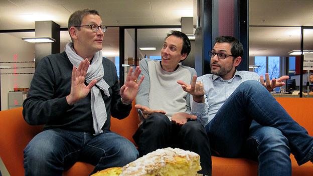 Toni Poltera, Stéphane Gabioud und Davide Gagliardi sitzen gestikulierend auf einem Sofa.