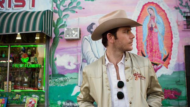 Sam Outlaw steht mit Cowboyhut vor einer farbigen Wand in Los Angeles.