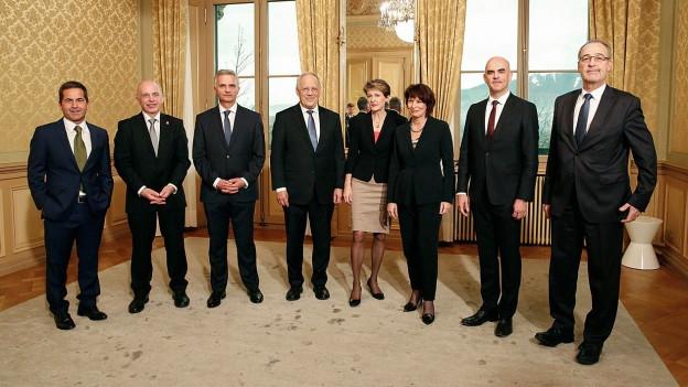 Der Bundesrat inklusive Bundeskanzler posiert in einem Zimmer.