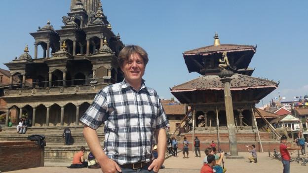 Jürg steht auf dem Patan Durbar Square in Kathmandu. Im Hindergrund sind zwei Tempel zu sehen, die vom Erdbeben verschon blieben.
