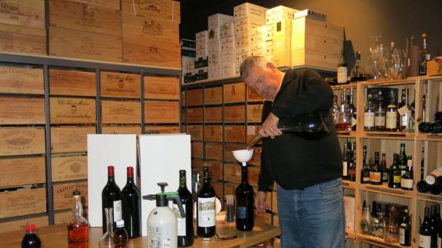 René Gabriel dekantiert in seinem Weinkeller eine Flasche Rotwein.