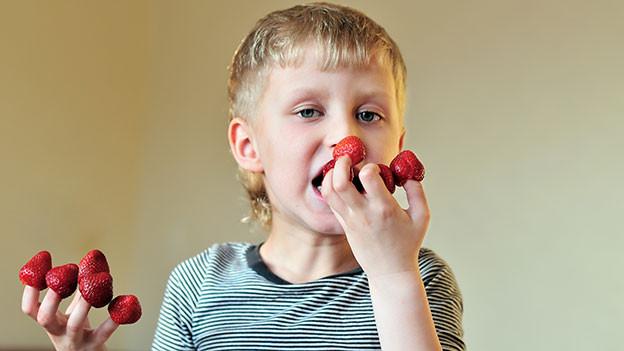 Ein Kind hat auf jedem Finger eine Erdbeere aufgesteckt. Es hält die eine Hand an den Mund.