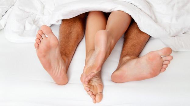 Füsse unter der Bettdecke.