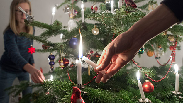 Die Kerzen vom Weihnachtsbaum werden angezündet.