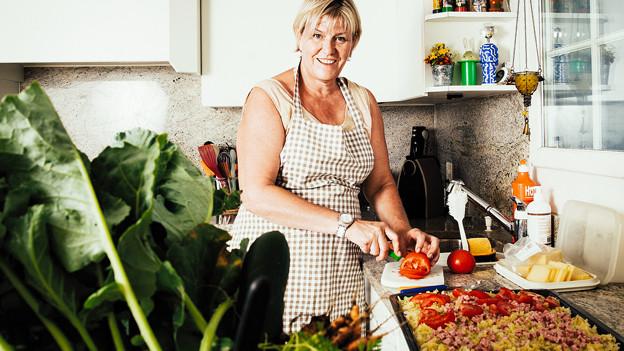 Eine blonde Frau steht in der Küche und schneidet eine Tomate.