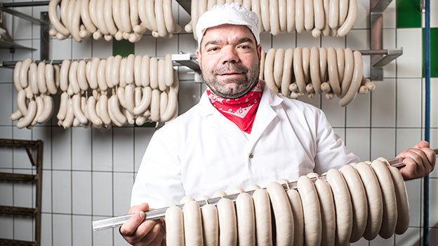 Metzger hält viele Glarner Kalberwürste in den Händen.