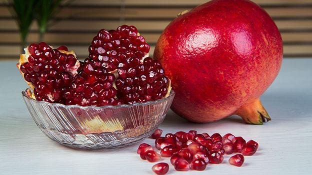 Granatapfel ganz und daneben eine Glasschüssel mit Granatapfelkernen.