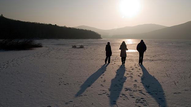 Drei Leute stehen in verschneiter Landschaft.