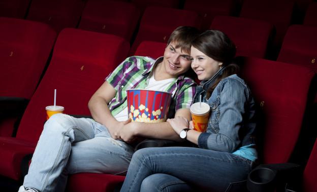 Zwei junge Leute sitzen vergnügt im Kino, mit Popcorn und Getränken