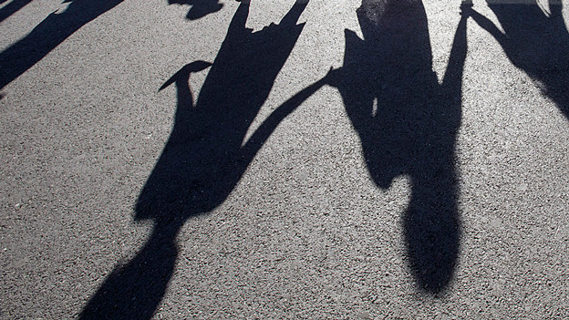 Schatten einer Menschenkette auf dem Asphalt.