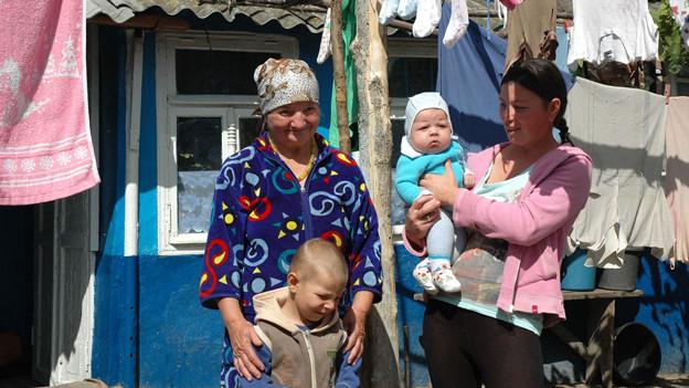 Eine alte Frau steht mit ihrer Tochter und zwei Kindern vor dem Haus.