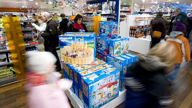 Kinder und Erwachsene in der Spielwarenabteilung.