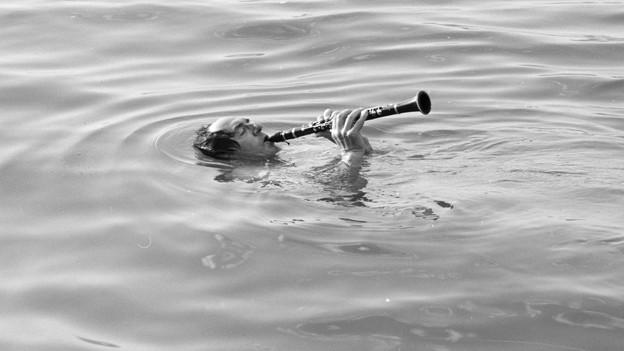 Mann mit Klarinette im See schwimmend.