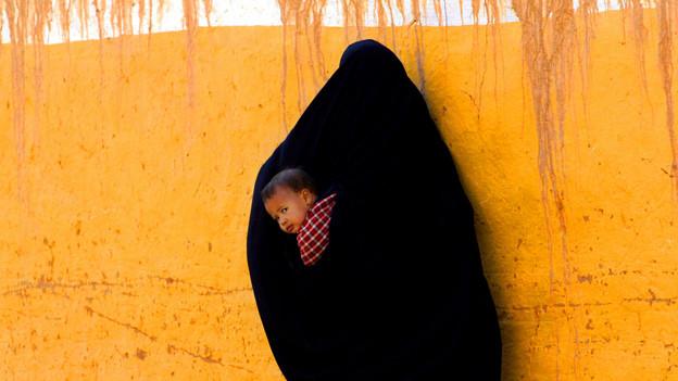 Frau schwarz verhüllt trägt ein Kind auf dem Rücken.