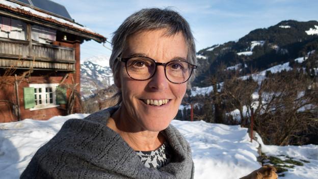 Porträt Daniela Gemsch. Sie steht vor ihrem Haus in den Bündner Bergen.