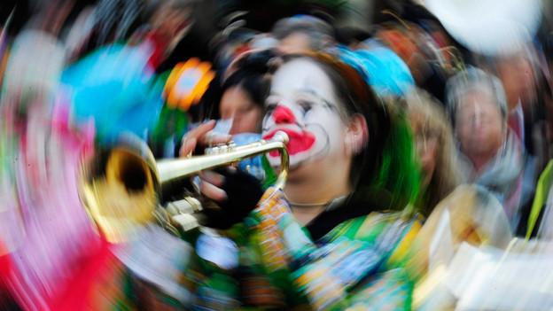 Fasnächtler spielt auf der Trompete.