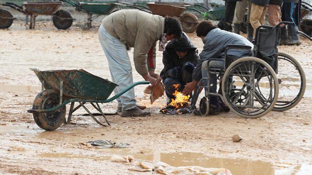Flüchtlingskinder wärmen sich in Jordanien an einem offenen Feuer.