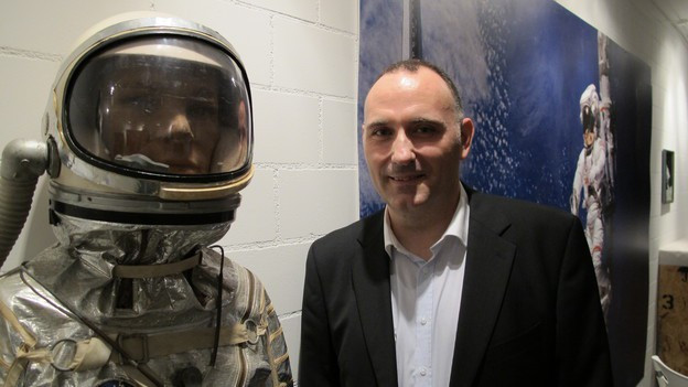 Guido Schwarz steht neben einem Raumanzug.
