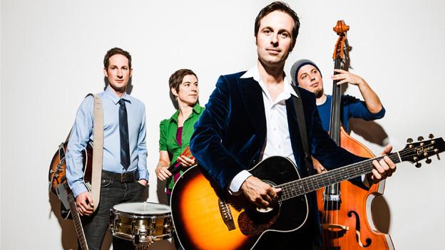 Die vier Bandmitglieder posieren mit ihren Instrumenten.
