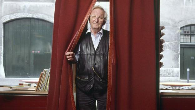 Peter Bichsel betritt einen Raum durch einen roten Vorhang.