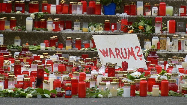 Inmitten von Trauerkerzen steht ein weisses Schild, auf dem steht: «Warum?»