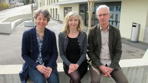 Regina Aklin, Anita Richner und Ernst Hörler sitzen auf einer Mauer.