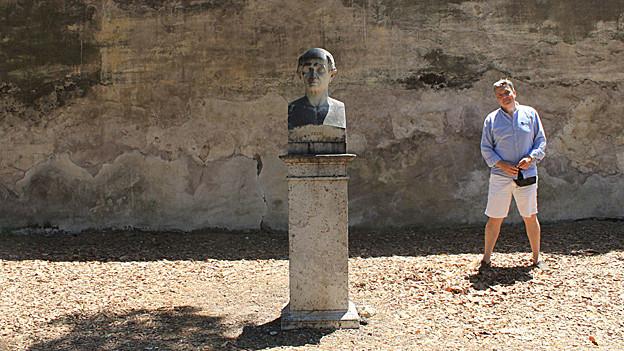 Mann steht neben einer Büste.