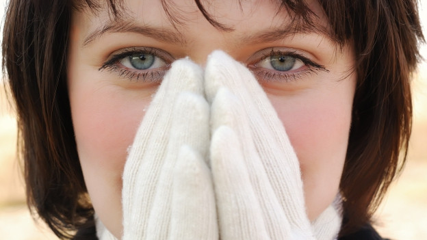 Frau hält Hände mit Handschuhen vor das Gesicht.