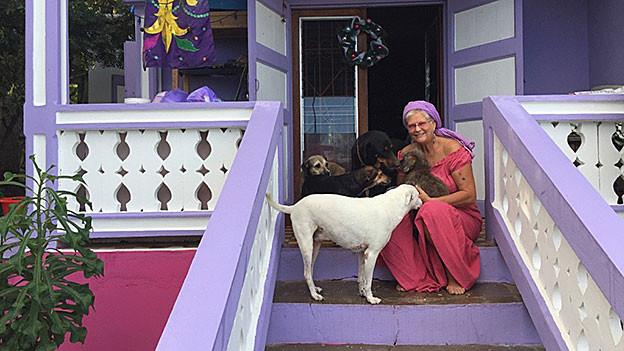 Ursula Oppikofer sitzt umringt von ihren Hunden auf einer Treppe vor dem Haus.