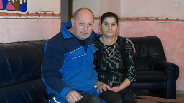 Beat Steiner sitzt mit seiner Frau auf einem schwarzen Sofa.