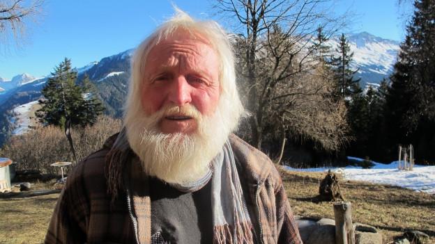 Bergführer und Künstler Gübi Luck mit langem weissen Bart vor bündner Bergkulisse.