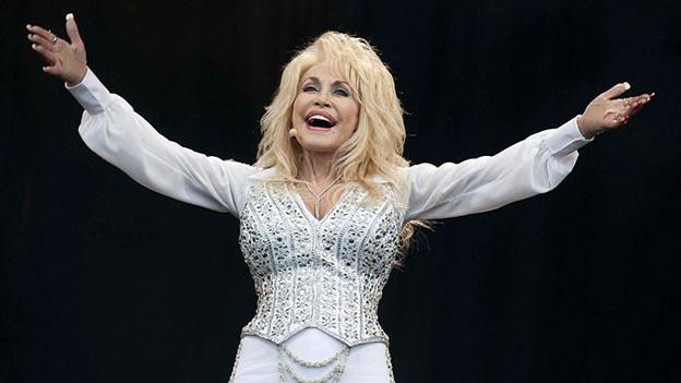Dolly Parton in weissem Kleid auf der Bühne.