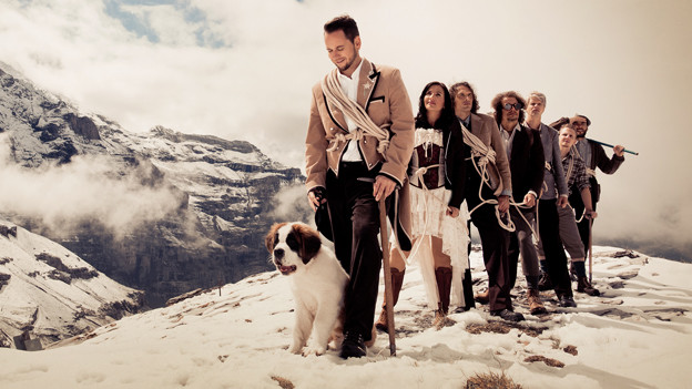 Trauffer mit Bernhardinerhund und Band im Schnee.