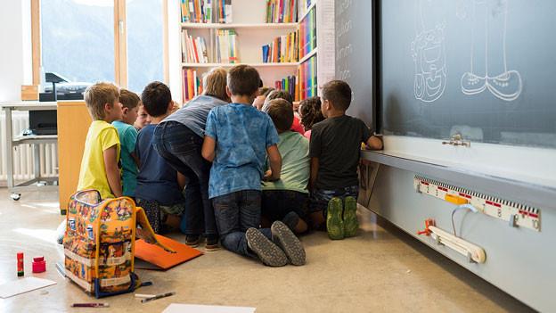 Schulkinder sitzen im Schulzimmer vor der Wandtafel am Boden.