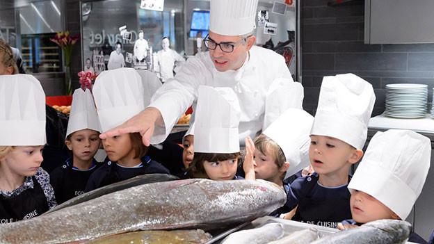 Koch mit Mütze zeigt Kindern in der Küche einen grossen Fisch.