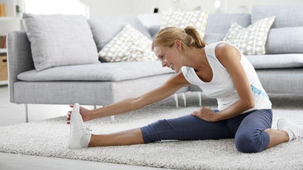 Frau macht Dehnübung im Wohnzimmer.