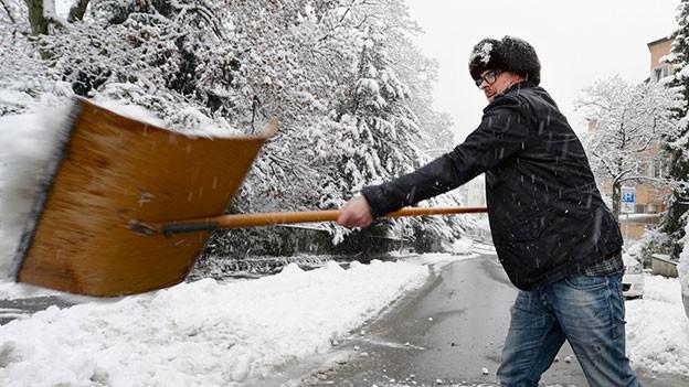 Mann mit Mütze räumt mit einer Schaufel Schnee weg.