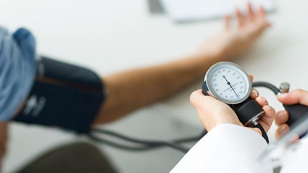 Arzt hält Blutdruckmessuhr in der Hand.