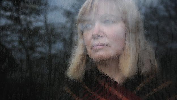 Eine Frau steht hinter einem Fenster, auf dem sich Regentropfen gesammelt haben.